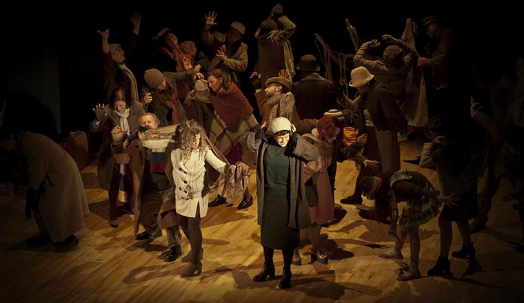 scena di uno spettacolo teatrale con persone disperate sul palco