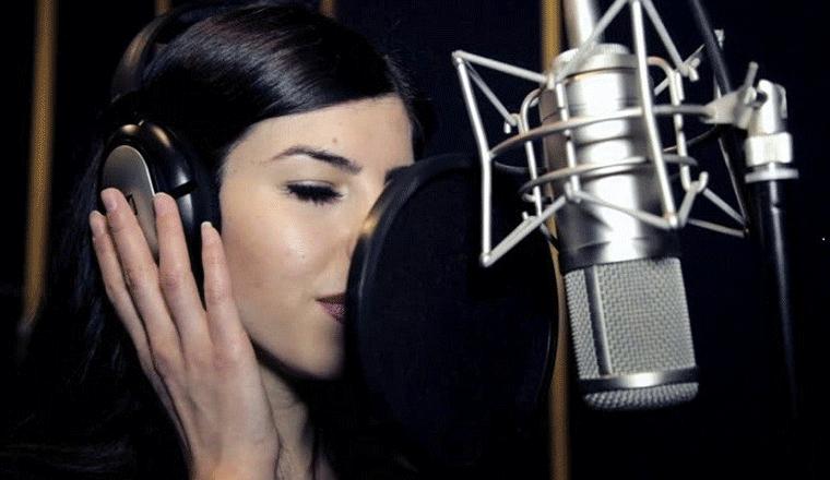 ragazza con cuffia al microfono in studio di registrazione